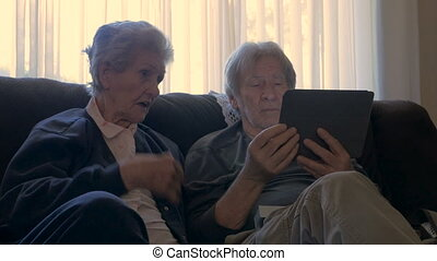Two seniors sit next to each other and talk while holding a mobile tablet dolly