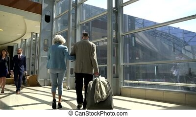 Two seniors walking with suitcase