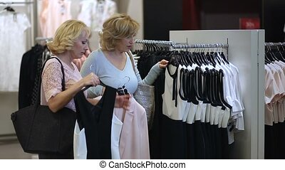 Two senoir women at boutique choosing dress.