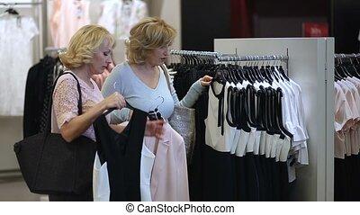 Two senoir women at boutique choosing dress. - Two best...