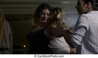 Two sensual women dancing with each other fooling around at disco club