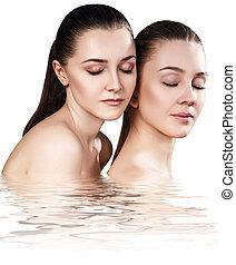Two sensual women in water.