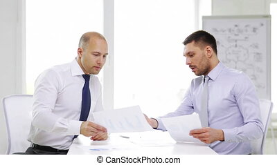 two serious businessmen with charts in office