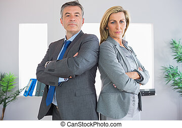 Two serious mature businesspeople looking at camera standing firmly back to back with crossed arms at office