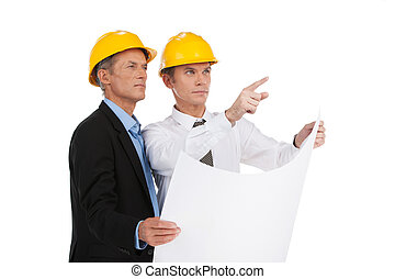 two serious older man standing. engineer showing foreman building plan