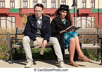 Two serious people sitting on bench reading book