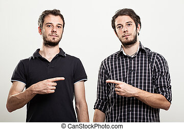 Twins Pointing Each Other - Two Serious Twins Pointing Each...