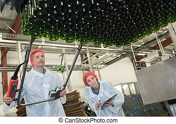 two serious workers doing their job on factory production line