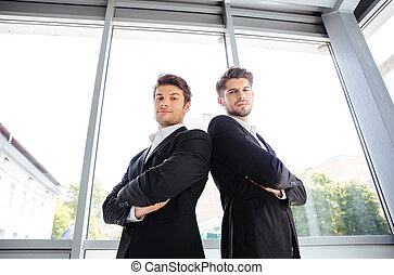 Two serious young businessmen standing with arms crossed in office