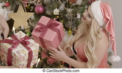 Two sexy female Santas showing presents in their hands to each other near the Christmas tree, slow motion.