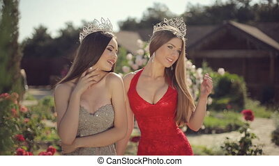 Two sexy young female in the long gowns and crowns smiling...