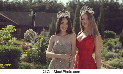 Two sexy young girls in evening gowns and crowns smiling and...