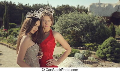 Two sexy young women posing in evening gowns and crowns in a beautiful garden