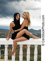 Two sexy young women sitting on a white handrail