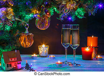 Two shampagne glasses with candeles and christmas tree