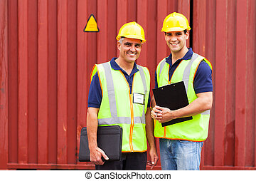shipping company workers standing in front of containers