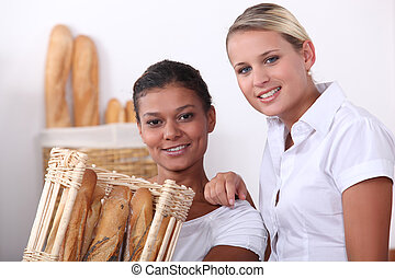 Two shop assistants working in a bakery