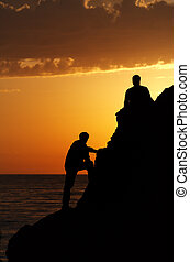 Two silhouette of people in beautiful sunset
