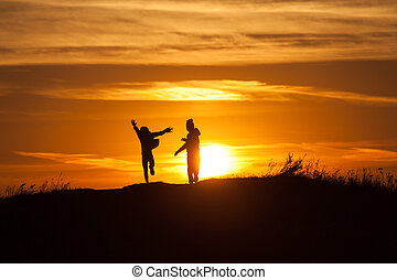 Two silhouettes of a child at sunset background