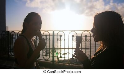 Two silhouettes of young women sitting on the quay and...