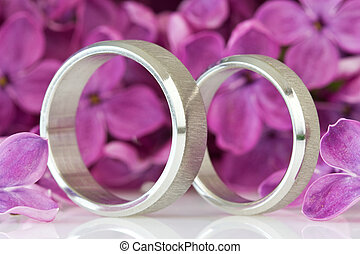 rings with lilac flowers in the background