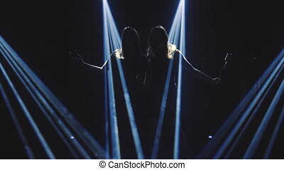 Two singers in the smoke and blu light sings into a retro microphone and dance. Black background. Silhouette