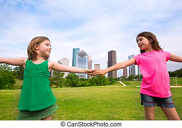 Two sister girls friends playing holding hand in urban...
