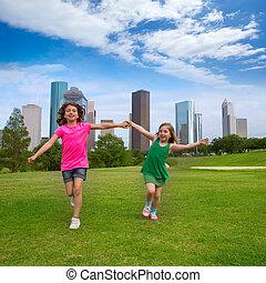Two sister girls friends running holding hand in urban skyline