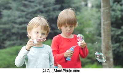 Two sisters are blowing bubbles in the park, Slow motion. Close up