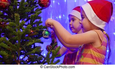 Two sisters beautiful girls decorate a Christmas tree with toys and garlands