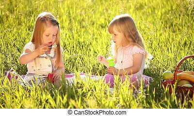 Two sisters blow bubbles