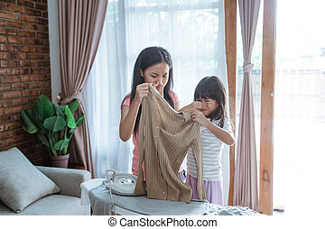 two sisters closed his nose by his finger when holding a smell clothes