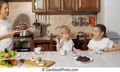 Two sisters drink tea with sweets and talk whle their mother brings cake.