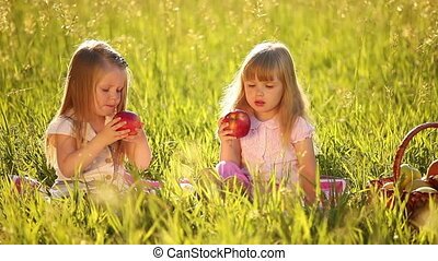 Two sisters eating apples in the me