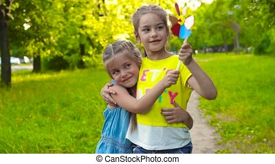 Two sisters girls holding colorful pinwheel - Two sisters...