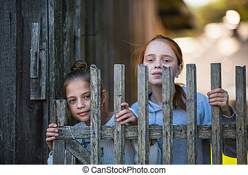 Two sisters girls look out from behind a wooden village fence.