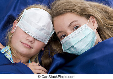 sisters in bed with protective mask