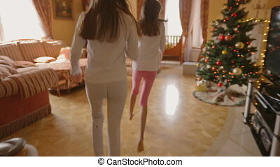 Two sisters in pajamas running in living room to open their...