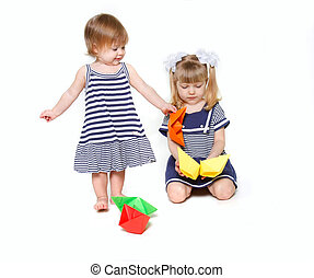 two sisters in sailor dresses with paper ships over white