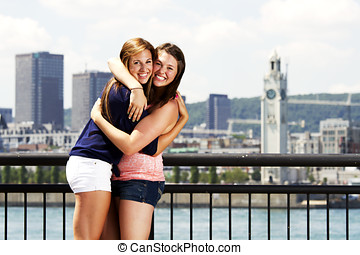 Two sisters interacting with city behind