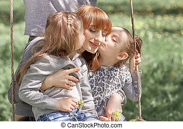 two sisters kiss their mother on a walk