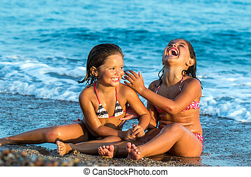 Two sisters laughing together on beach.