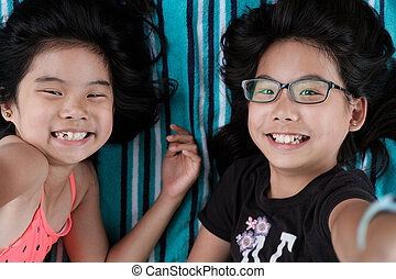 Two sisters laying down taking selfie photo