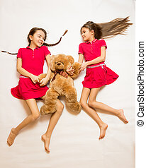 two sisters lying on floor and playing with teddy bear