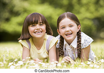 Two sisters lying outdoors smiling