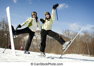 Two sisters on mountain top excited to be skiing