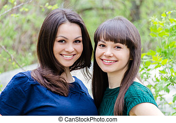 Two sisters or girl friends smiling, laughing and hug outdoors in spring or summer
