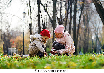 Two sisters playing in autumnal park