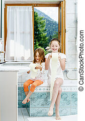 Two sisters playing with toilet paper roll