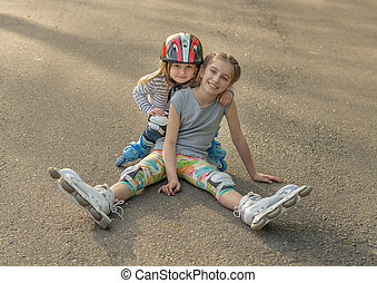 Two sisters roller skating together, wearing protection